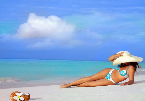 attractive woman in hat lying on the beach